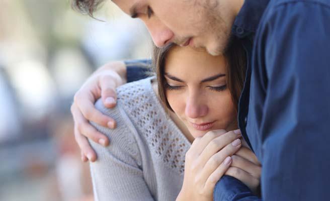 恋人の彼女の肩を抱く男性