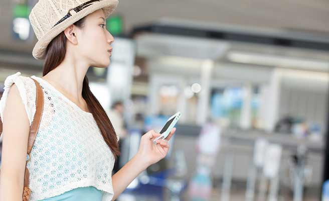 空港で連絡を待つ女性