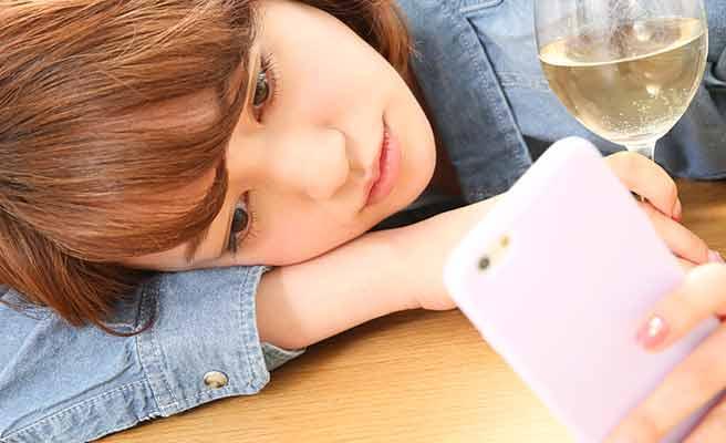 スマホとお酒を傍らに寂しい表情の女性