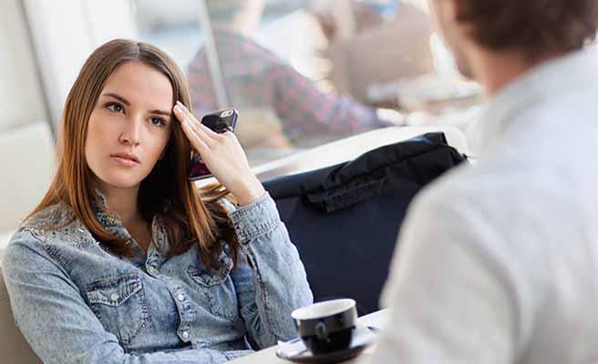 喫茶店で彼氏の顔を顔をじっと見つめる女性