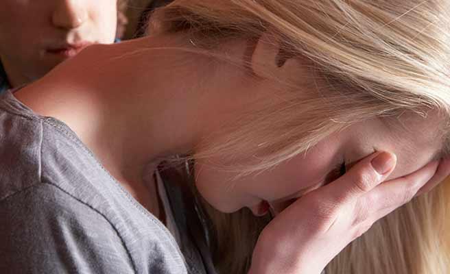 顔を手で覆って俯く女性
