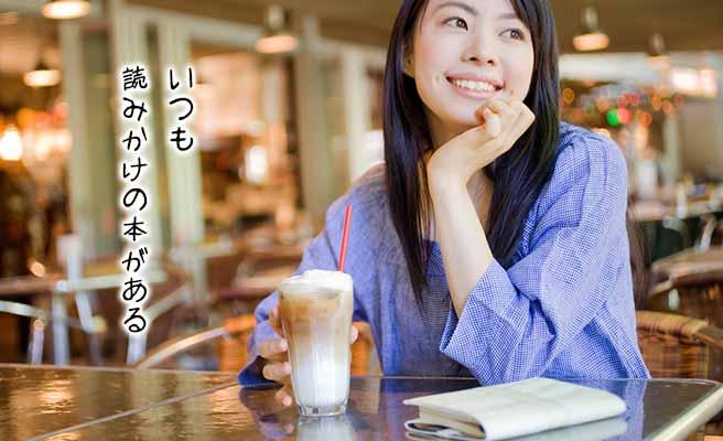 喫茶店で飲み物の傍に本を置く女性