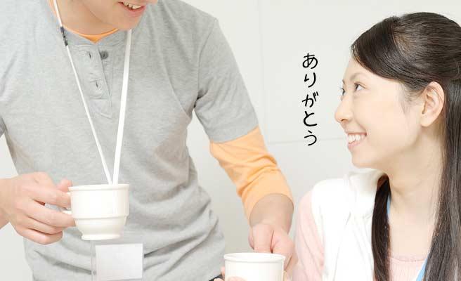 女性にコーヒーを持ってくる男性