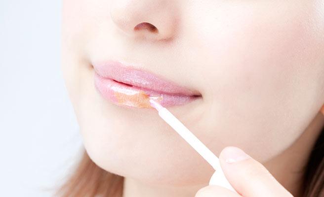 蜂蜜を唇に塗る女性