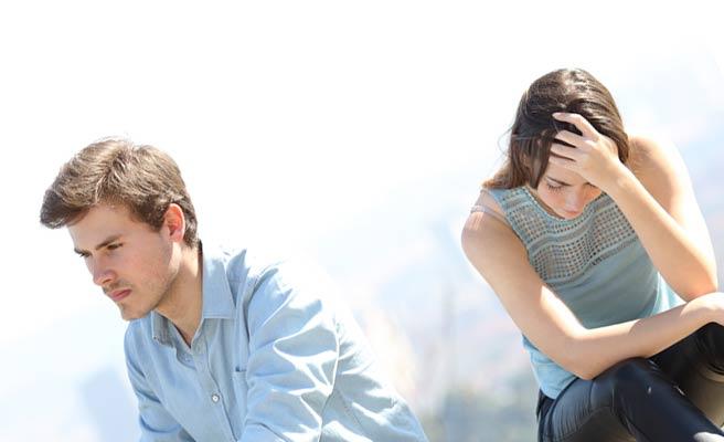 無言で座る彼氏の傍らで頭を抱える彼女