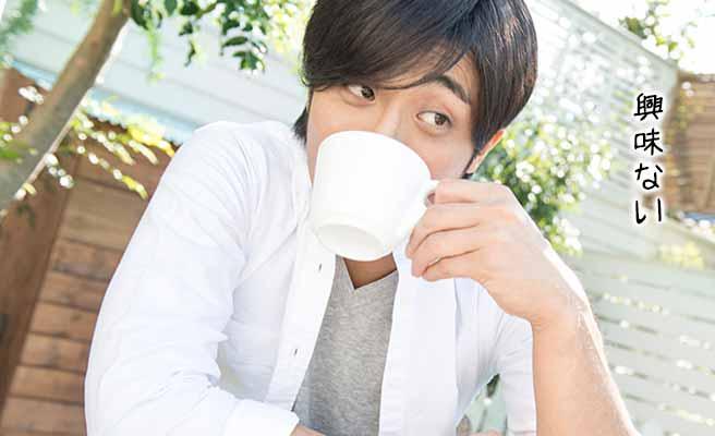 コーヒーを飲みながら視線を横へ向ける男性