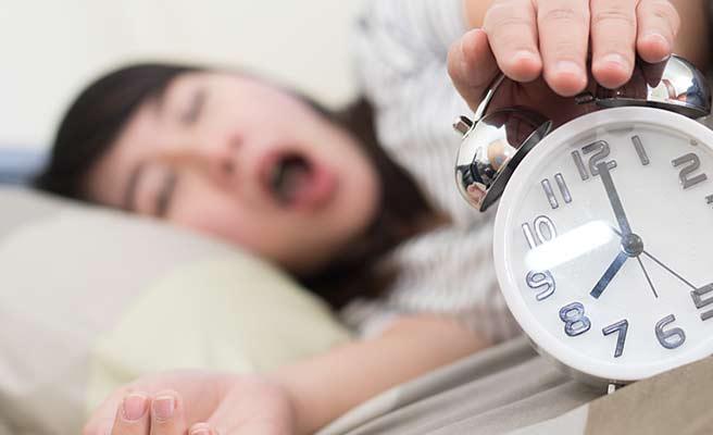 目覚まし時計を止める女性