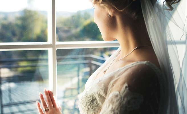 ホテルの窓から外を見る花嫁