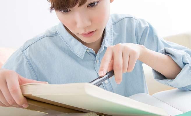 本を開いて勉強する女性