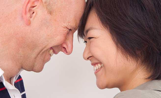 額をつき合わせて笑顔の日本人女性と外国人男性のカップル