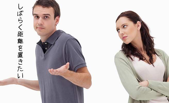 距離をおきたいとお手上げポーズの男性と睨む女性