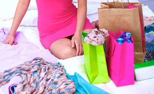 紙袋や衣類に囲まれて座る女性