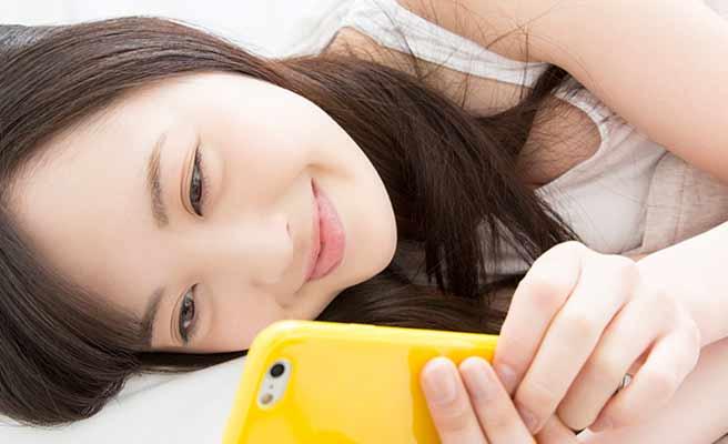 寝ながらスマホを見つめる女性
