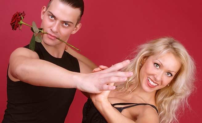 バラを口に咥えた彼氏と踊る女性