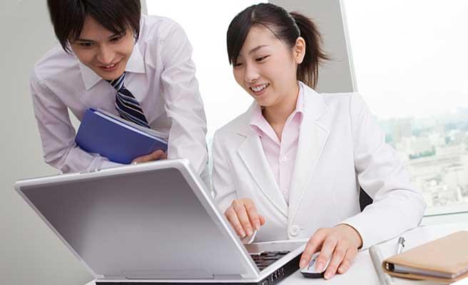 パソコンを操作する女性社員と覗き込む男性社員