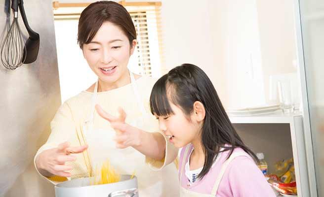 料理する母親と手伝う娘