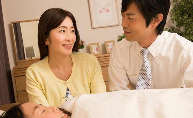 寝ている子供の前で会話する男女