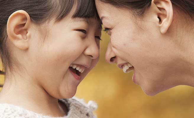 互いに頭を付き合わせて笑う母親と娘