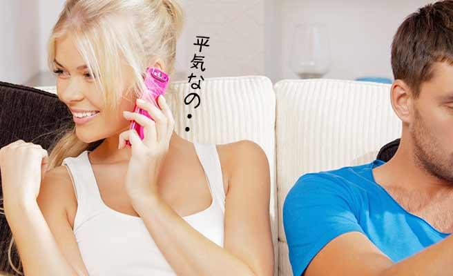 彼氏の隣で電話する女性