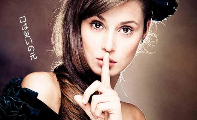 口元に指を立てて戒める女性