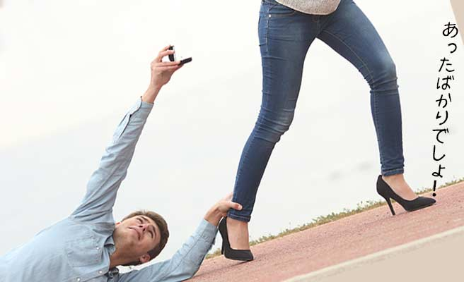 女性の足をつかんで指輪を渡そうとする男性