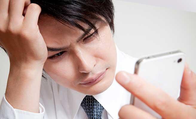仕事中の男性がスマホを見ながら頭を抱えている