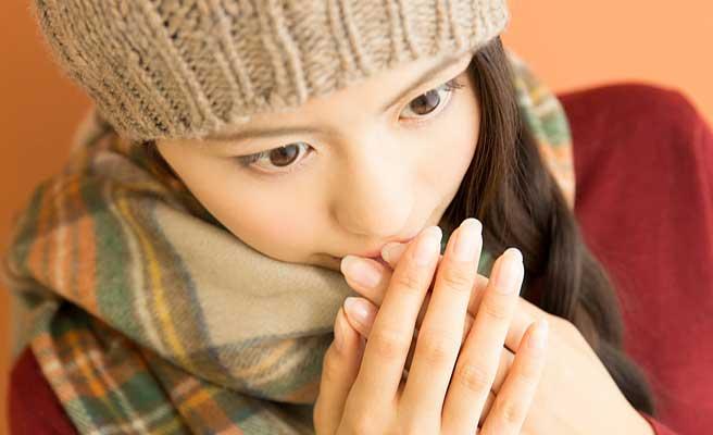 指先を口元で暖める女性