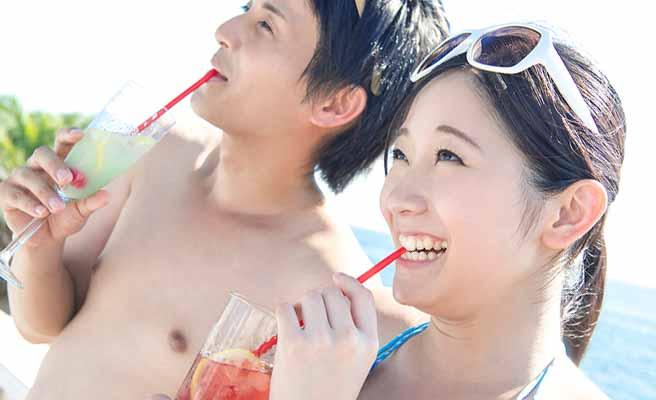 ビーチでジュースを飲むカップル