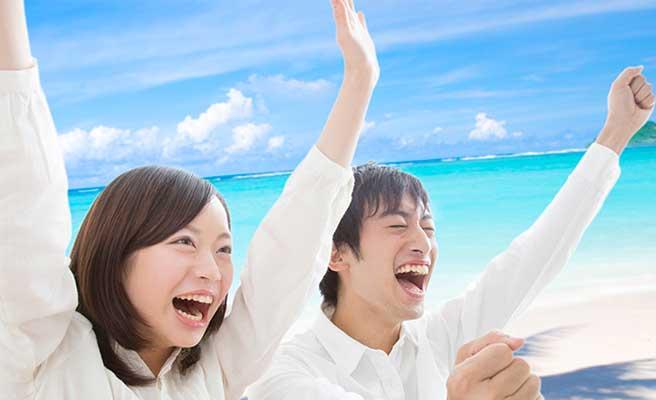 沖縄の青い海に喜ぶカップル