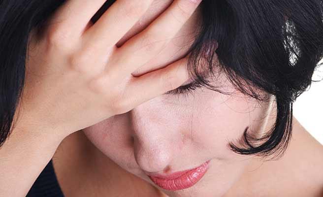 顔に手を当てて、悲しみにくれる女性