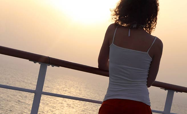 日没の海を見つめる女性