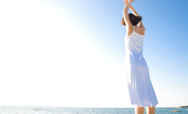 海と空に向かって背伸びする女性