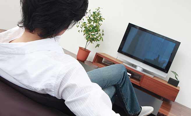 家でテレビを見る男性