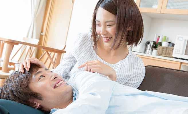 部屋で彼女の膝枕でくつろぐ男性