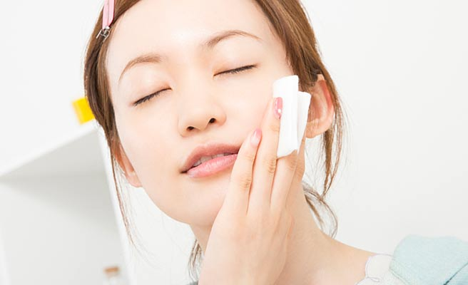 顔に美容液を当てて肌の手入れをする女性