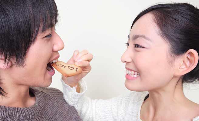 彼氏の口にクッキーを運ぶ女性