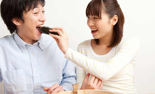 男性の口に海苔巻きを入れようとする女性