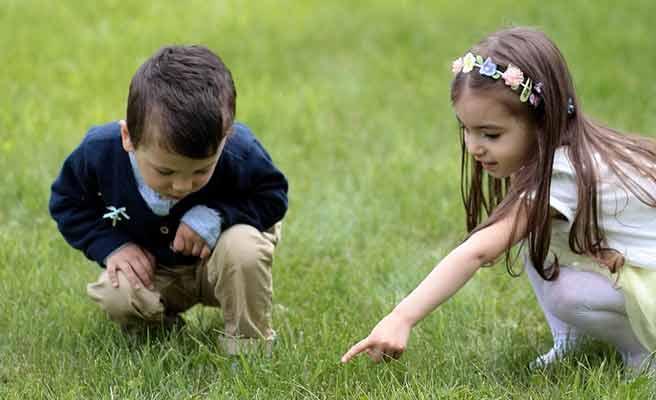芝生の上で一緒に遊ぶ男の子と女の子