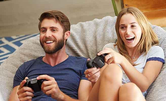 一緒にテレビゲームに興じるカップル