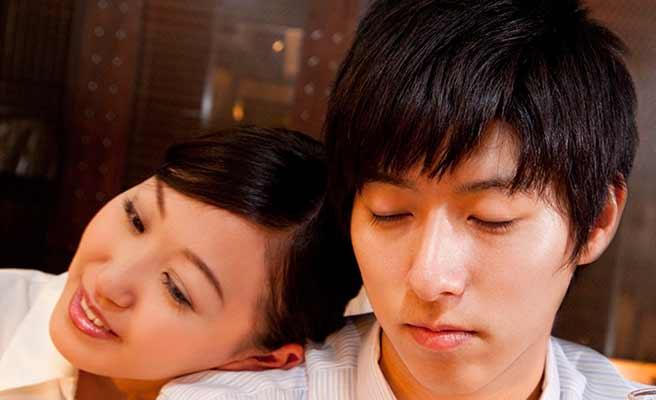 男性の肩にもたれかかる女性と目を閉じる男性