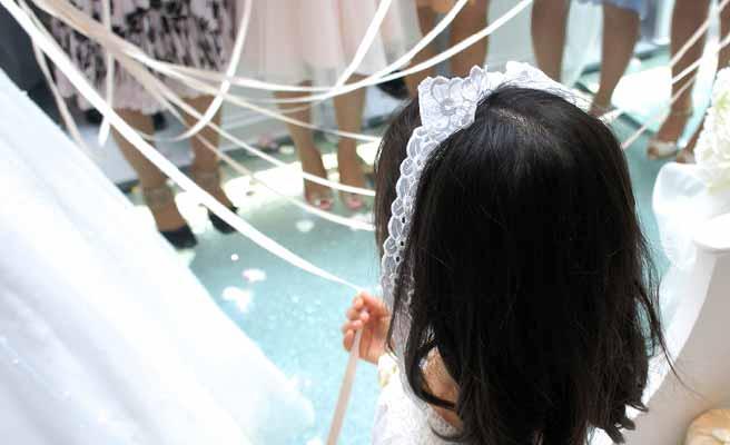 ブーケプルズの紐を握る大人たちに混じって参加する少女