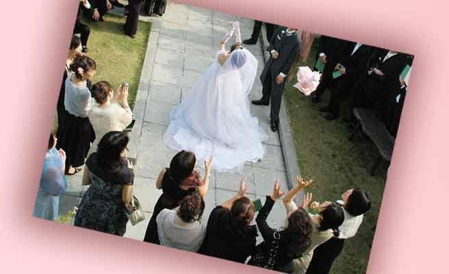 花嫁がブーケを背後に並ぶ女性ゲストに向かって投げる