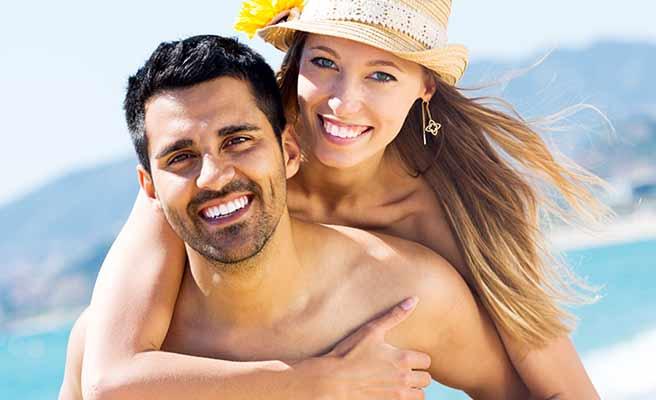 海辺で彼におんぶする女性