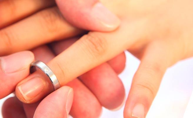女性の左手の薬指に指輪をはめる男性の手