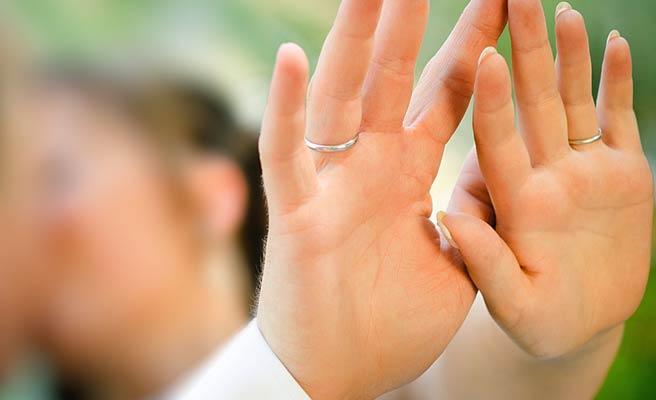 指輪をした手を並べて見せるカップル