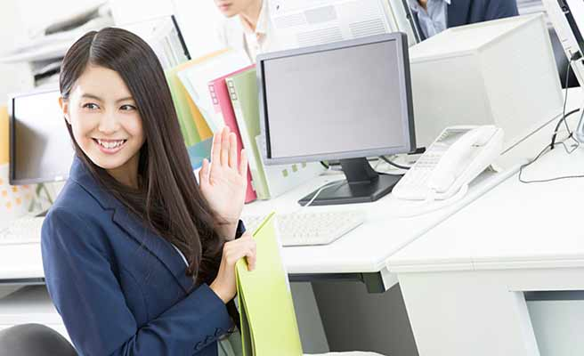 会社内で後ろを振り向いて軽く挨拶する女性