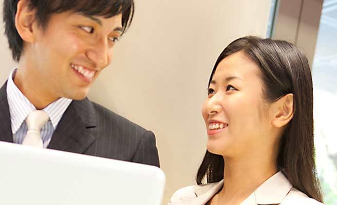 社内でパソコンを見ながら会話する男女