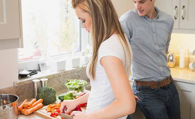 台所で料理を作る女性と傍で見守る男性