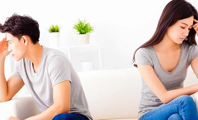 ソファに離れて座り互いに顔を背ける男女