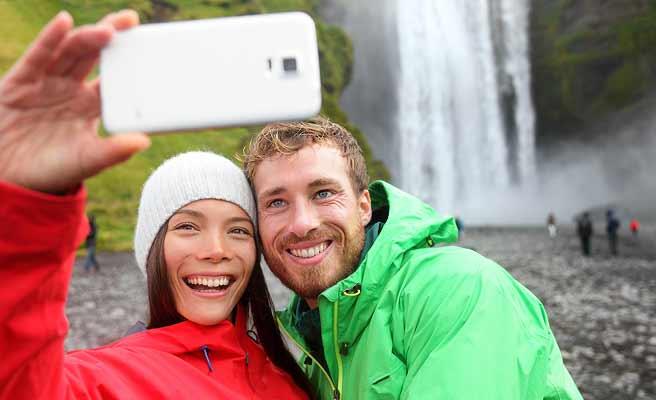 滝の前で記念撮影するカップル